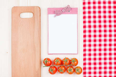 Recipe cookbook, cherry tomatoes, checkered tablecloth, plank on wood background photo