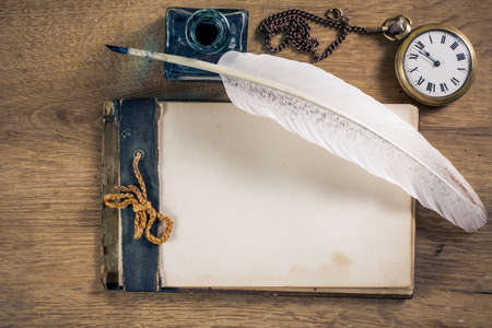 Old notebook, quill and pocket watch on wood Archivio Fotografico
