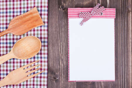 Recipe notebook, tablecloth, spoon, fork on wood texture background photo