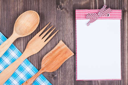 Recipe cook book, kitchen textile, wooden spoon, fork on wood textured background photo