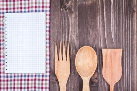 white linen: Kitchen textile, wooden spoon, fork, recipe book on wood textured background