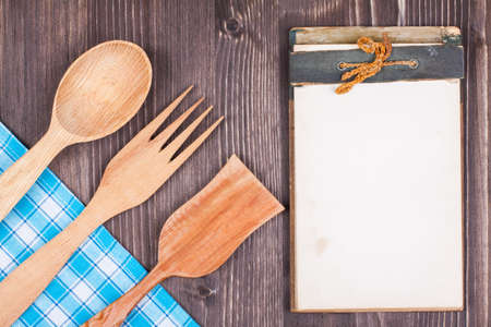 Recipe cook book, kitchen tablecloth, wooden spoon, fork on wood textured background