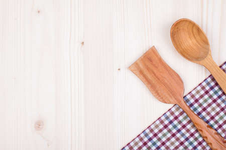 Kitchen tablecloth, wooden spoon, fork on table background photo
