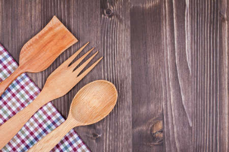 Checkered tablecloth, fork, spoon on wood background photo