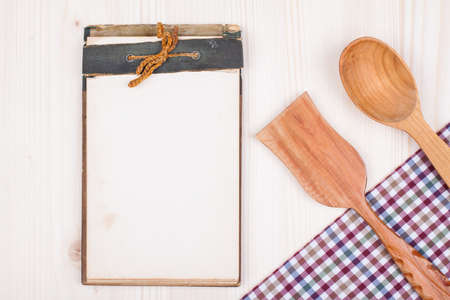 books on a wooden surface: Recipe cook book, kitchen textile, wooden spoon, spatula on wood textured background