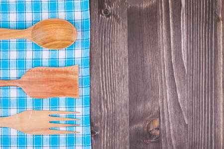 Kitchen tablecloth textile, wooden spoon, fork, spatula on wood background