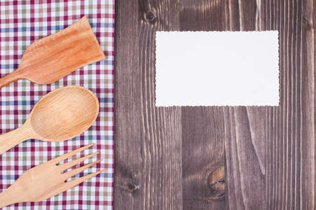 books on a wooden surface: Kitchen tablecloth, spoon, fork, spatula, paper card on wood background Stock Photo