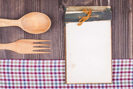 Recipe notebook, tablecloth, spoon, fork on wood texture background