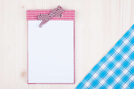 Recipe cook book, blue tablecloth on wood background