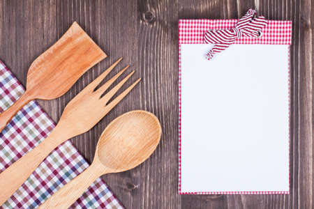 Recipe cook book, kitchen textile, wooden spoon, fork on wood textured background