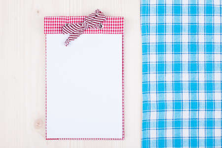 red tablecloth: Recipe cook book and tablecloth on wooden texture background