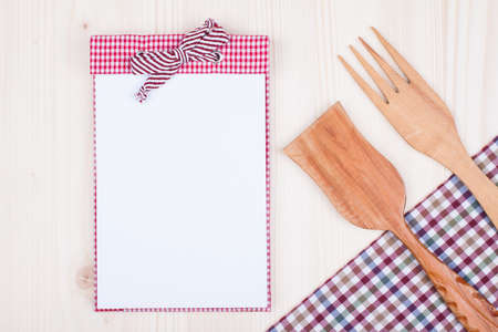 Recipe cook book, fork, spatula, checkered tablecloth on wood background photo