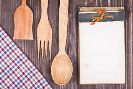 books on a wooden surface: Recipe cook book, kitchen tablecloth, wooden spoon, fork on wood textured background