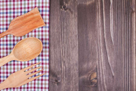 Checkered tablecloth, fork, spoon, spatula on wood background photo