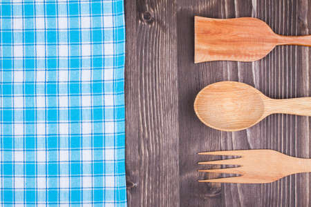 Blue kitchen tablecloth, wooden spoon, fork, spatula on wood background photo