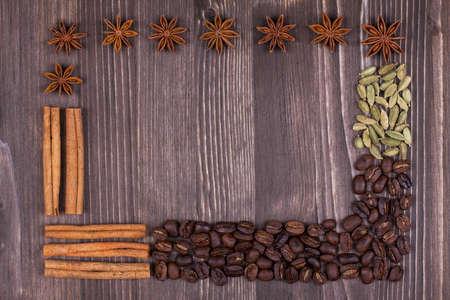 anise: Frame of coffee beans, cinnamon, star anise, cardamom on wood background