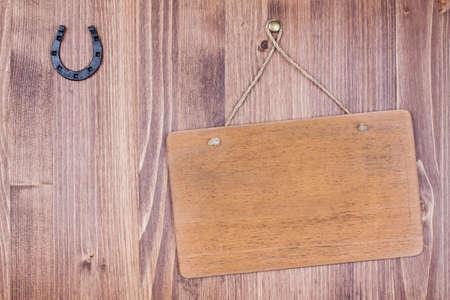 herradura: Letrero de madera con una cuerda que cuelga en los tablones de fondo con la herradura