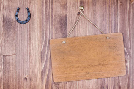 Wooden signboard with rope hanging on planks background with horseshoe Imagens