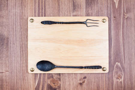 Menu or recipe wooden board blank, spoon, fork on wood background photo