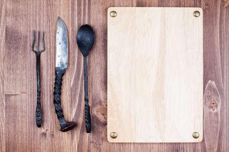 recipe card: Menu wooden board blank, spoon, fork, knife on wood background