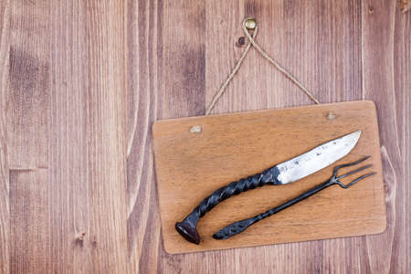 Wooden sign board with knife and fork hanging wall background Stock Photo - 19741997