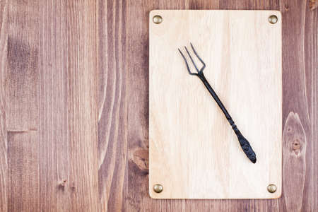 Wooden signboard with fork on wood background photo