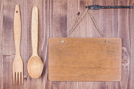 Wooden signboard hanging planks wall background, spoon, fork