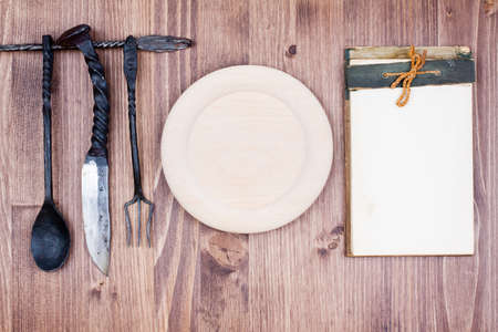 Cook book, wooden plate, spoon, fork, knife on wood background photo