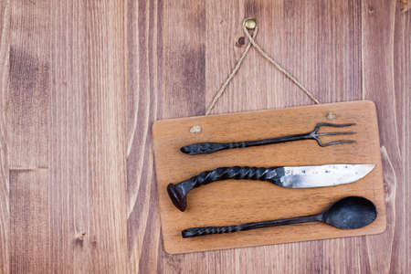 Wooden signboard hanging with knife, spoon and fork on wall background Stock Photo - 19742000