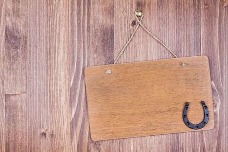 horseshoe vintage: Wooden signboard with horseshoe hanging on planks background Stock Photo