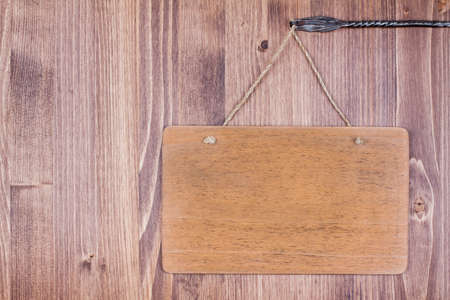 Wooden signboard with rope hanging on planks background Stock Photo - 19742012