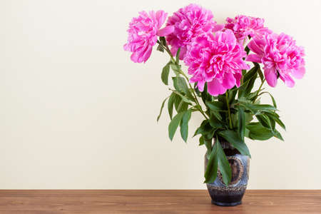 Peony flowers bouquet in vintage vase on wooden table photo