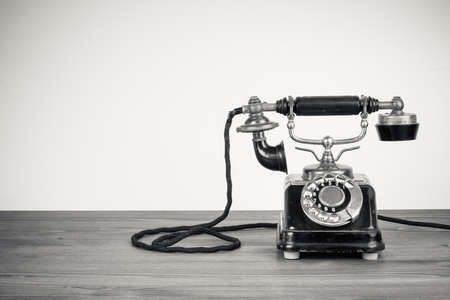 rotary dial telephone: Vintage old telephone on wood table black and white photo