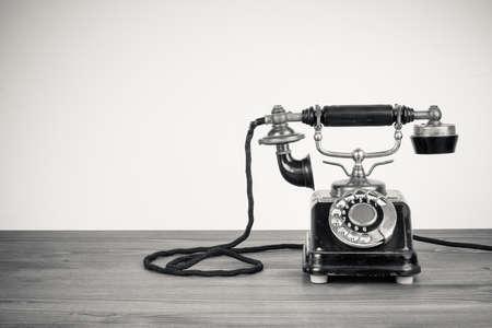 Vintage oude telefoon op houten tafel zwart-wit foto Stockfoto