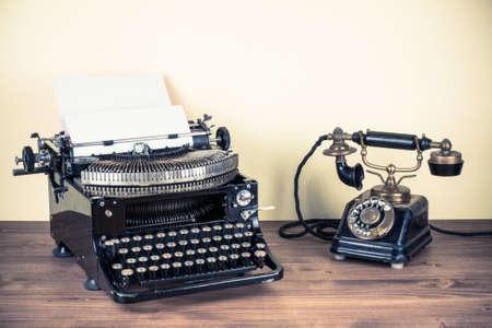 Vintage telephone, old typewriter on table