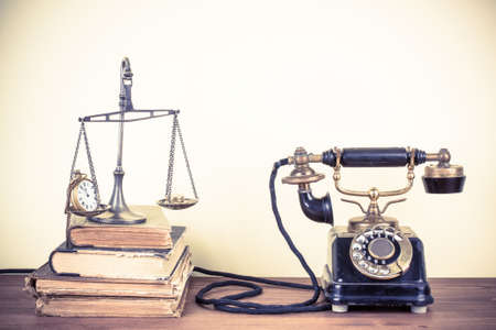 Vintage old telephone, scales with watches and money, books on wood table