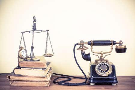 telefono antico: Vintage vecchio telefono, bilance con orologi e denaro, libri sul tavolo in legno Archivio Fotografico