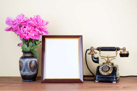 Vintage old telephone, frame and flowers on table