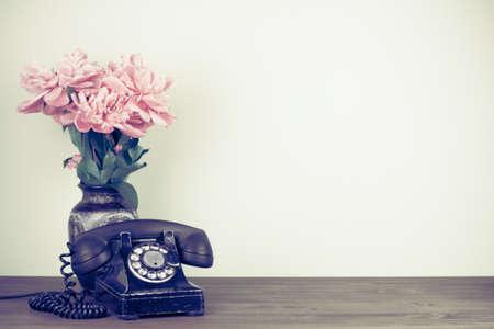 Retro zwarte oude telefoon en bloemen op tafel