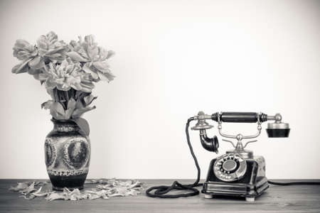 Vintage old telephone and flowers on table sepia photo