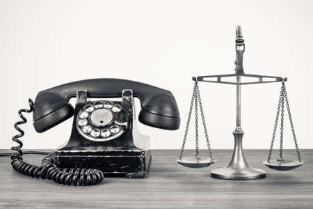 jury: Retro old telephone and scales on wood table.