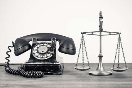 jurado: Viejo teléfono retro y escalas en la mesa de madera.