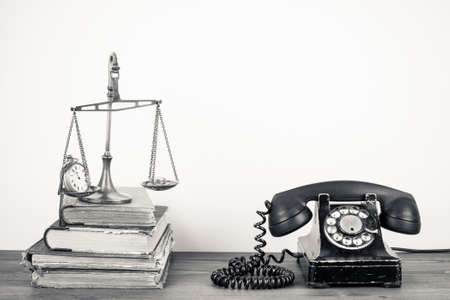 Old telephone, scales with watches and money, books on wood table  Vintage sepia photo photo