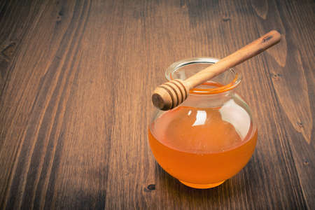 Honey jar on wooden table  Vintage toned photo