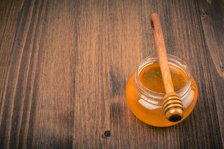 Honey jar on wooden table background  Vintage toned photo