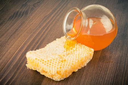 Honeycomb and honey jar on table background photo