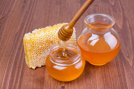 Honeycomb and honey pots, dipper on wooden table photo