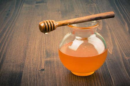 Honey jar on wooden table. Vintage toned photo