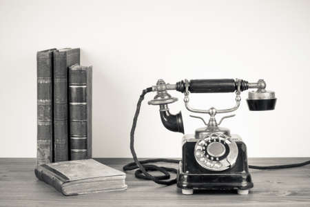 Vintage telephone, old books on table sepia photo