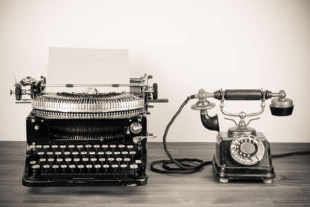 secretarial: Vintage typewriter and telephone old style sepia photography